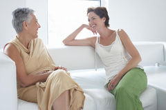 Мать и дочь говоря на софе Стоковые Изображения RF