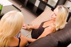 Мать и дочь говоря на софе Стоковая Фотография