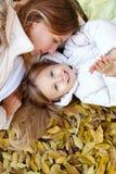 Мать и дочь лежа на листьях осени Стоковое Изображение