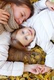 Мать и дочь лежа на листьях осени Стоковое Фото