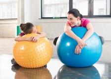 Мать и дочь лежа на шариках фитнеса и усмехаясь одине другого Стоковая Фотография