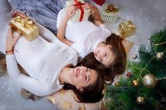 Мать и дочь лежа под рождественской елкой Стоковая Фотография RF