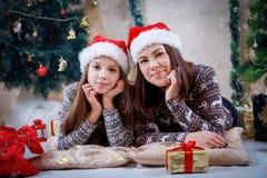 Мать и дочь лежа под рождественской елкой Стоковые Фотографии RF