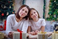 Мать и дочь лежа под рождественской елкой стоковые изображения