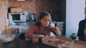 Мать и дочь есть пиццу в кухне видеоматериал