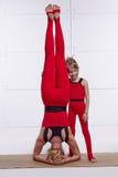 Мать и дочь делая йогу работают, фитнес, спортзал нося такие же удобные tracksuits, женщину семьи спаренную спорт Стоковое фото RF