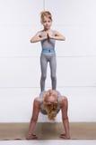 Мать и дочь делая йогу работают, фитнес, спортзал нося такую же удобными женщину спаренную спорт p семьи tracksuits Стоковые Изображения RF