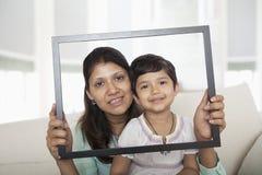 Мать и дочь задерживая картинную рамку и смотря через ее Стоковые Изображения RF