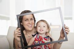Мать и дочь задерживая картинную рамку и смотря через ее Стоковые Изображения