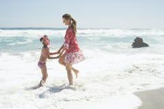Мать и дочь играя в воде стоковая фотография