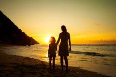 Мать и дочь играя на пляже стоковое изображение rf