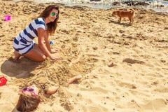 Мать и дочь играя на пляже Стоковые Фотографии RF