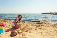 Мать и дочь играя на пляже Стоковые Изображения RF