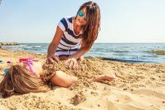 Мать и дочь играя на пляже Стоковые Изображения