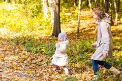Мать и дочь играя совместно в парке осени Стоковое фото RF
