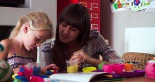 Мать и дочь играя с глиной моделирования в спальне сток-видео