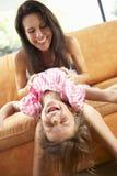 Мать и дочь имея потеху на софе Стоковое Изображение