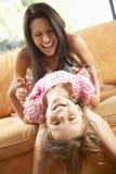 Мать и дочь имея потеху на софе Стоковая Фотография