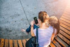 Мать и дочь используя телефон в парке стоковая фотография rf