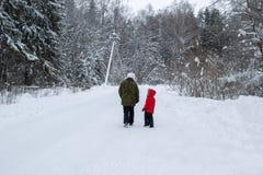 Мать и дочь идя вдоль дороги в лесе зимы Стоковая Фотография RF