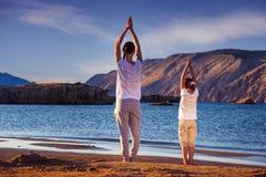 Мать и дочь, йога на пляже рано утром стоковые фотографии rf