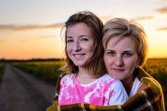 Мать и дочь на проселочной дороге на заходе солнца стоковые изображения