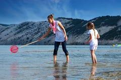 Мать и дочь на рыбной ловле пляжа стоковые фото