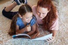 Мать и дочь на чтении ковра стоковые фото