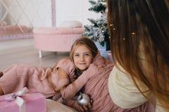 Мать и дочь обнимая около рождественской елки женщина и девушка с подарком на рождество Стоковое Изображение