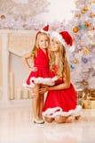 Мать и дочь одетые как Санта празднуют рождество Семья Стоковое Изображение