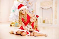 Мать и дочь одетые как Санта празднуют рождество Семья Стоковая Фотография