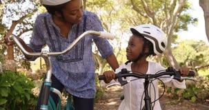 Мать и дочь подготавливают к ехать велосипеду видеоматериал