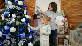 Мать и дочь подготавливают на праздник Нового Года, семья украшая рождественскую елку, счастливую семью дома внутри акции видеоматериалы