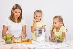 Мать и дочь подготавливая плодоовощ для juicing Стоковые Фотографии RF