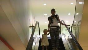 Мать и дочь получают вниз с эскалатора акции видеоматериалы