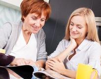 Мать и дочь прочитали кассету дома Стоковые Изображения RF