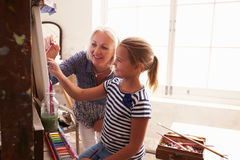 Мать и дочь работая на картине в студии искусства Стоковое фото RF