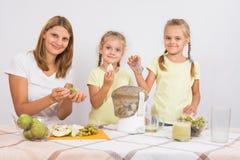 Мать и дочь сжимая сок от груш и виноградин Стоковые Фотографии RF