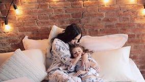 Мать и дочь сидят на кровати в пижамах и смотрят ТВ совместно Время семьи акции видеоматериалы