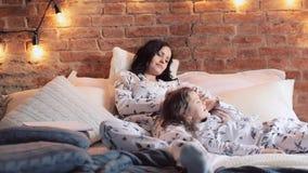 Мать и дочь сидят на кровати в пижамах и смотрят ТВ совместно Время семьи сток-видео