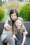 Мать и дочь сидя в природе и говоря selfie Стоковое фото RF