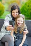 Мать и дочь сидя в природе и говоря selfie Стоковая Фотография RF