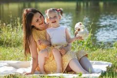 Мать и дочь сидя на белом одеяле Девушка держа белого медведя Мама смотрит ее дочь На заднем плане озеро Стоковое фото RF
