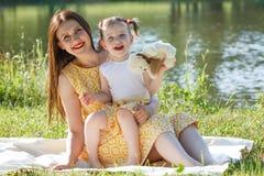 Мать и дочь сидя на белом одеяле Девушка держа белого медведя Посмотрите камеру На заднем плане озеро Стоковые Фотографии RF