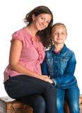 Мать и дочь сидя на деревянном комоде Стоковое фото RF