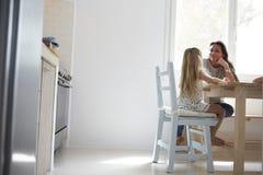 Мать и дочь сидя на кухонном столе и говорить Стоковое Изображение