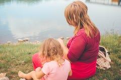 Мать и дочь сидя на пляже в славном летнем дне Стоковое Изображение