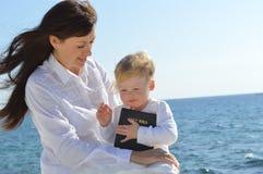 Мать и дочь сидя на пляже держа библию Стоковые Изображения RF