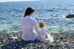 Мать и дочь сидя на пляже Стоковая Фотография