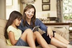Мать и дочь сидя на софе дома используя планшет стоковое фото